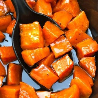 Big Spoonful of Candied Sweet Potatoes in Black Crockpot