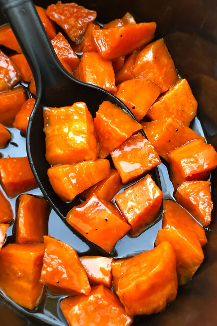 Spoonful of Candied Sweet Potatoes in Black Crockpot
