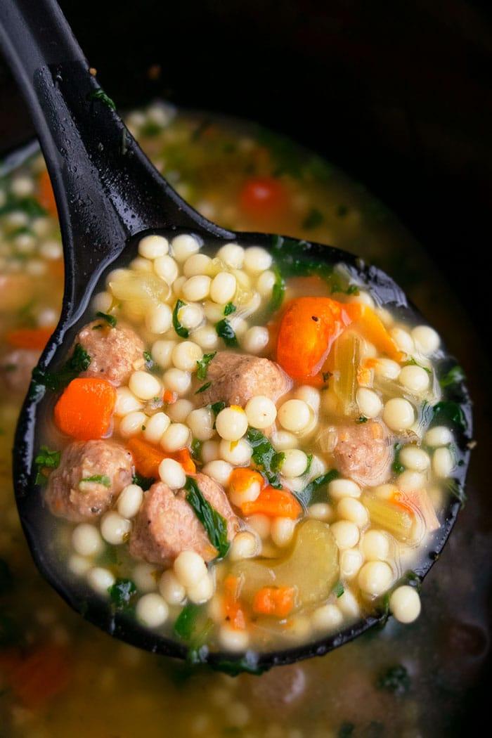 Spoonful of Italian Soup in Black Crockpot- Closeup Shot
