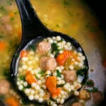 Easy Homemade Italian Wedding Soup in Black Slow Cooker with Black Spoon