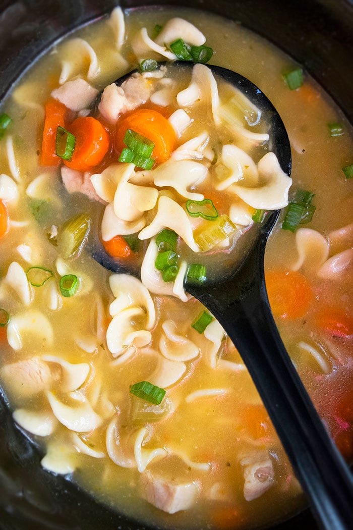 Hearty Chicken Soup With Noodles in Black Crockpot- Overhead Shot