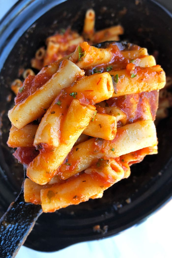 Spoonful of Tomato Penne Pasta Over Black Crockpot