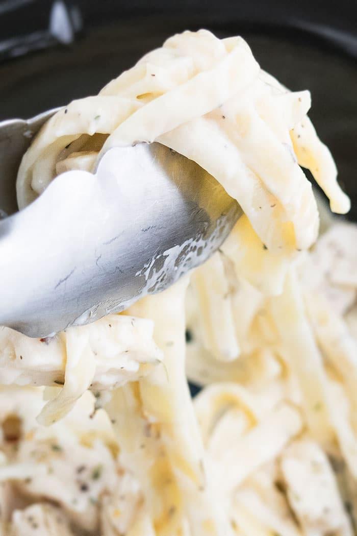 Closeup Shot of Tongs Loaded with Homemade Alfredo Pasta