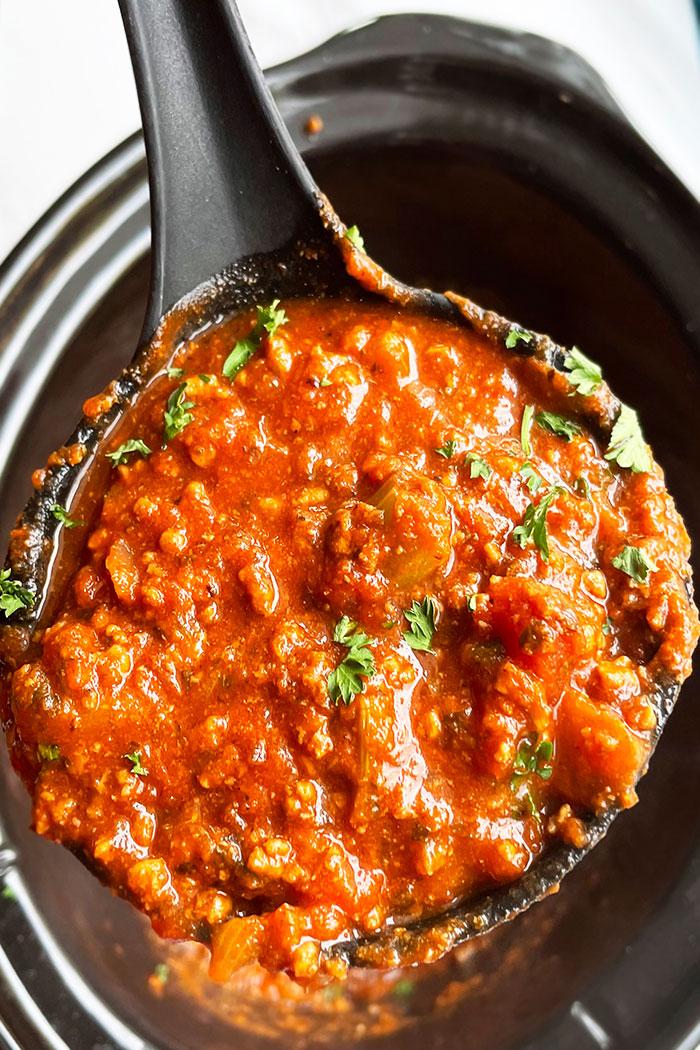 Spoonful of Spaghetti Bolognese Sauce Over Black Crockpot- Closeup Shot