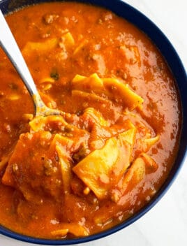 Easy Slow Cooker Lasagna Soup Served in Blue Bowl on White Background