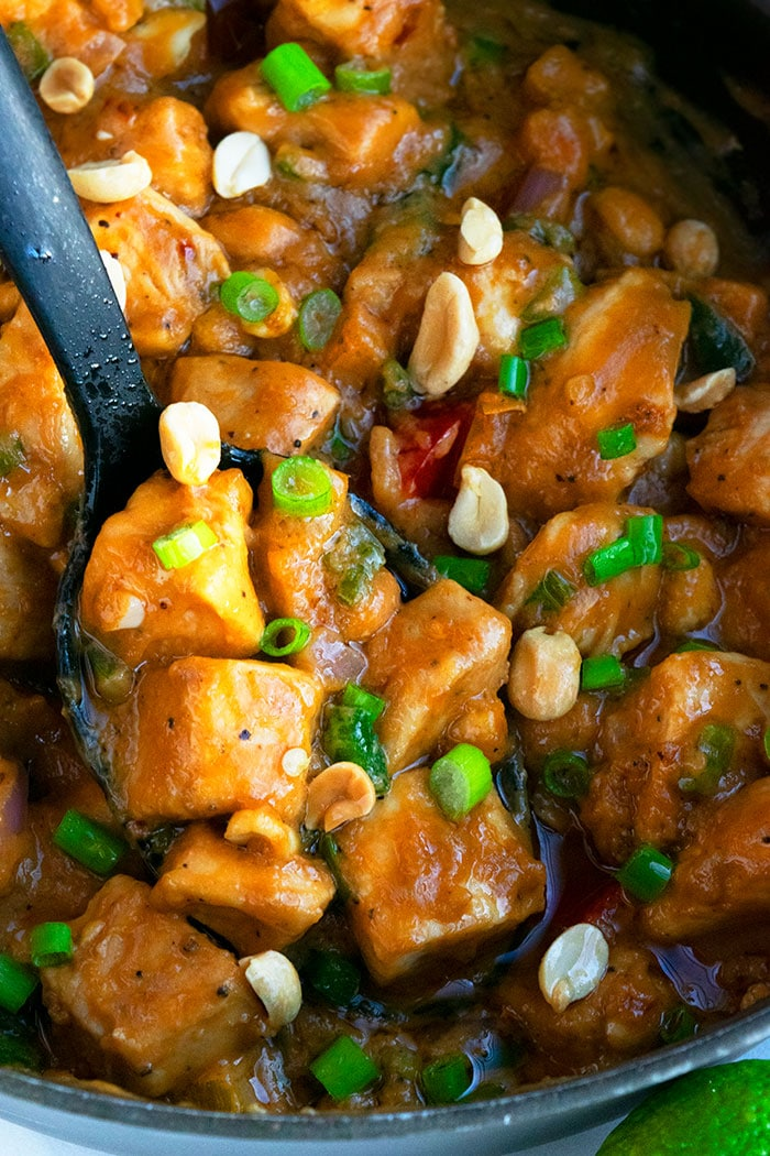 Spoonful of Thai Peanut Chicken in Black Slow Cooker