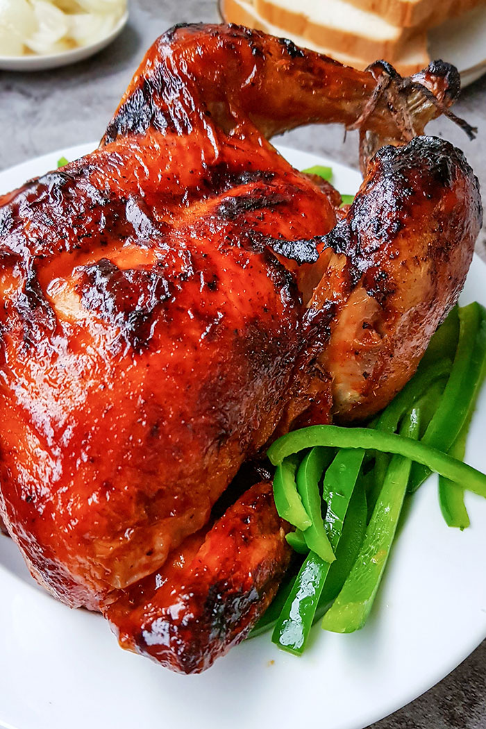 Closeup Shot of Spicy Tandoori Whole Chicken on White Plate with Green Peppers