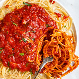 Easy Slow Cooker Vegetarian Mushroom Bolognese Served Over Pasta in White Plate