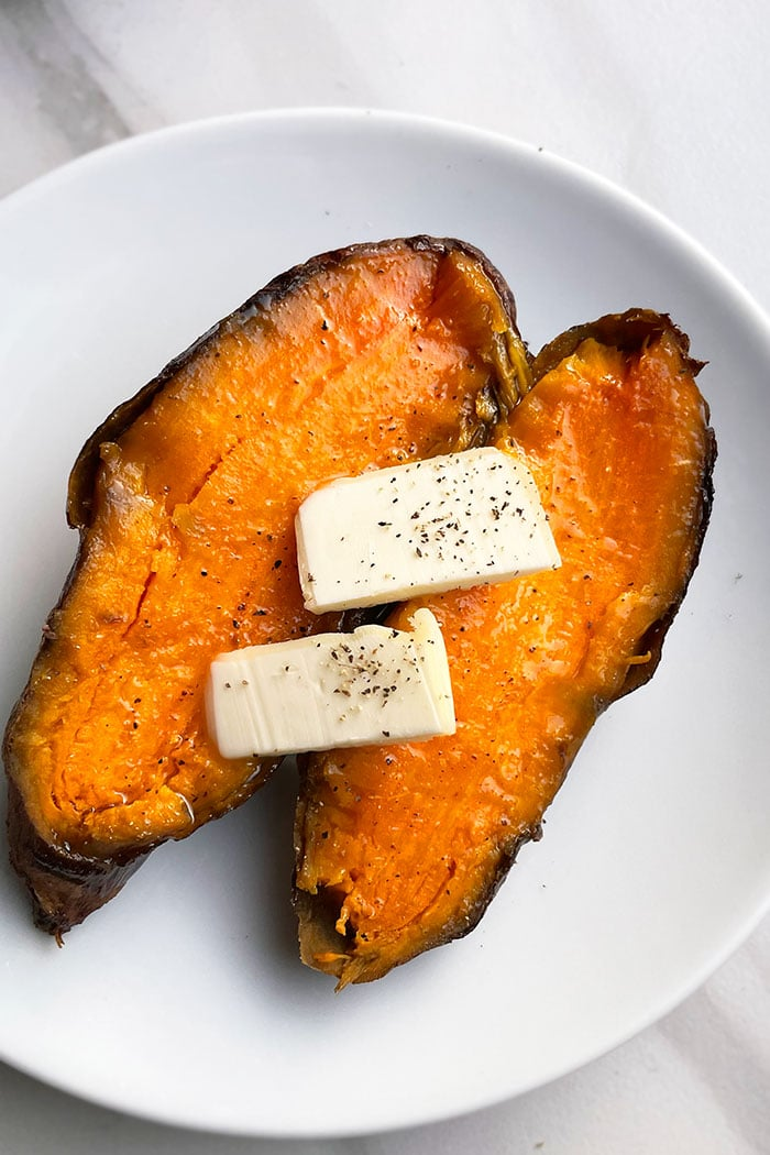 Baked Sweet Potatoes in White Plate, Topped with Slices of Butter