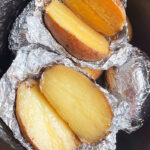 Baked Potatoes Wrapped in Foil in Black Slow Cooker