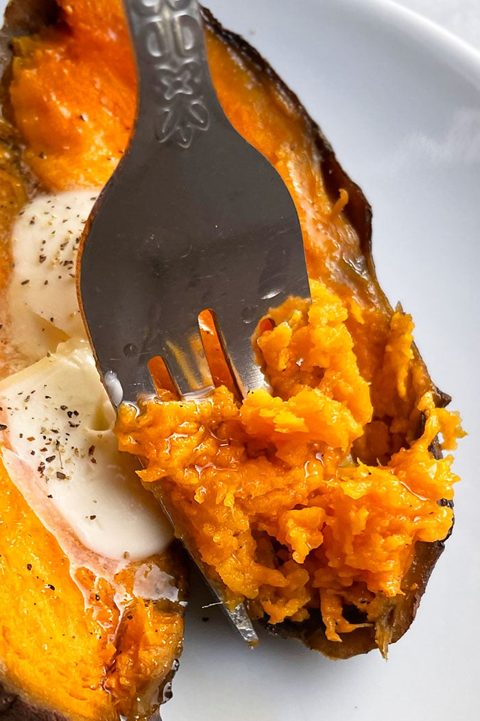 Closeup Shot of Fork Full of Sweet Potatoes in White Plate