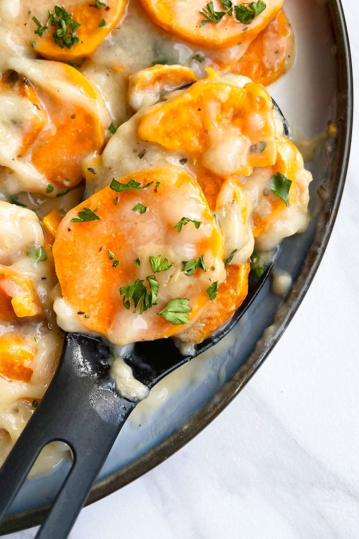 Spoonful of Cheesy Potato Au Gratin in White Plate Prepared in Crockpot