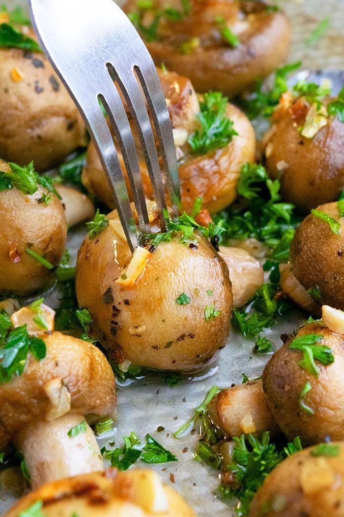 Fork Holding Garlic Butter Mushrooms- Closeup Shot