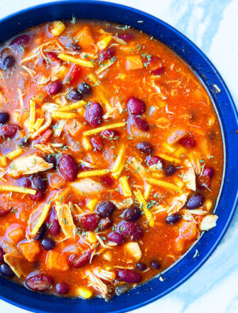 Easy Slow Cooker Mexican Chicken Enchilada Soup Served in Blue Bowl on Marbled Background